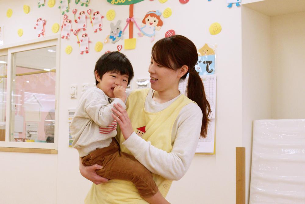 先生が笑顔でお子さんを抱っこしている写真