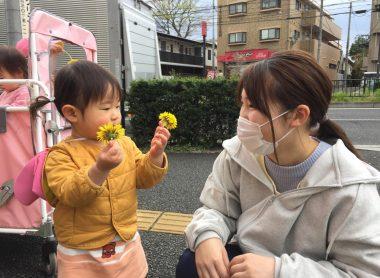 先生とお子さんが笑顔でたんぽぽを見ている写真