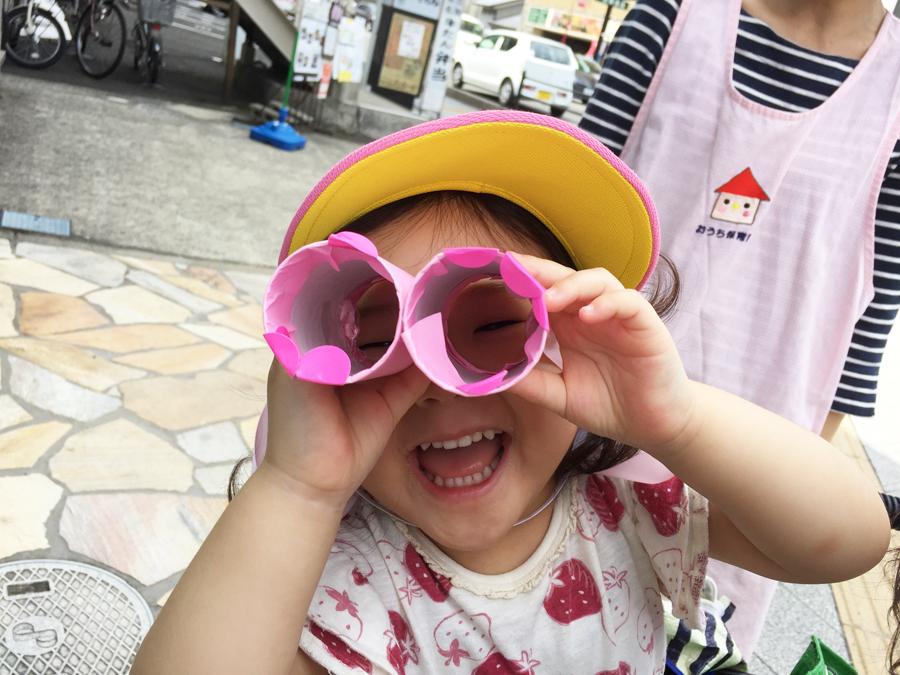 自分の双眼鏡を覗いてニコニコ笑顔のお子さんの写真