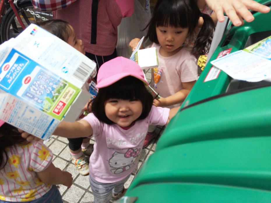 牛乳パックを笑顔で分別しているお子さん