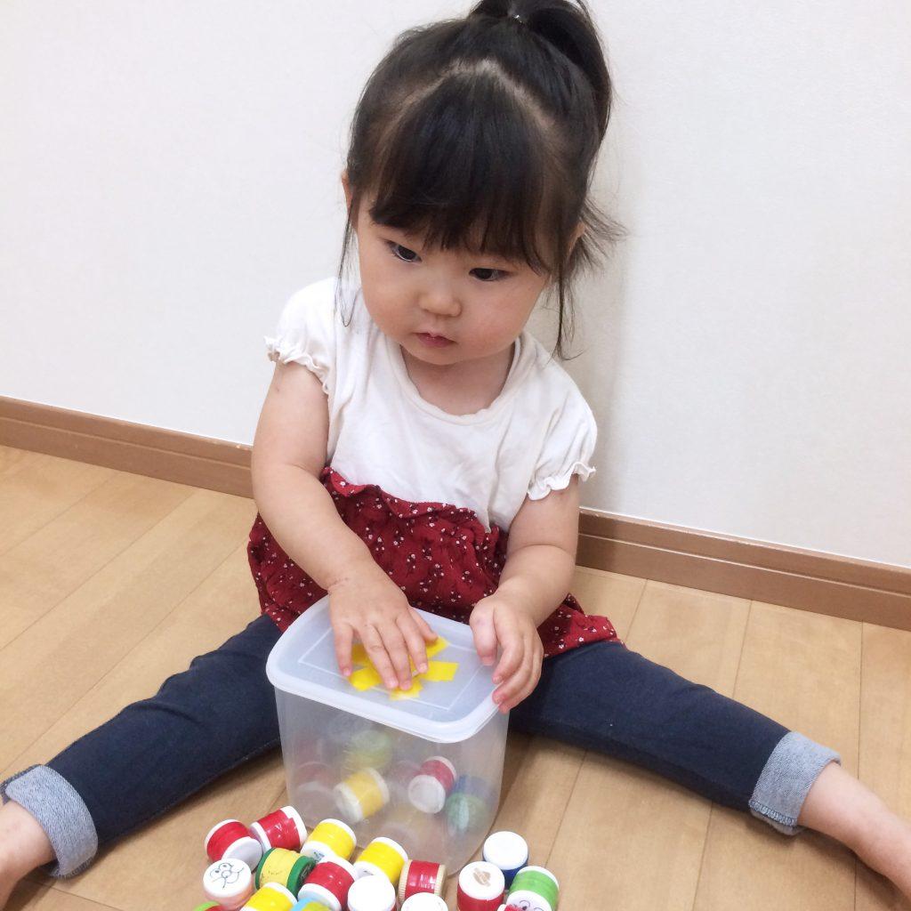 ペットボトルの蓋のおもちゃで遊ぶお子さん