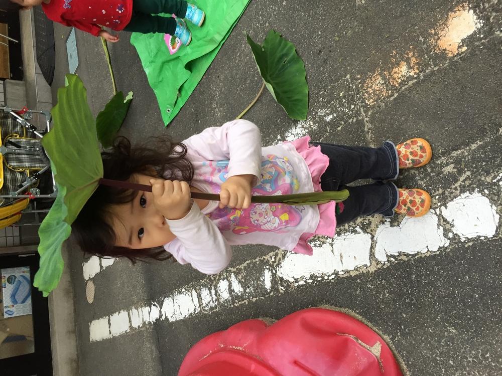 葉っぱを傘にしているお子さん