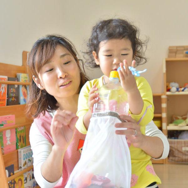 手作りおもちゃで遊ぶ子どもと保育士