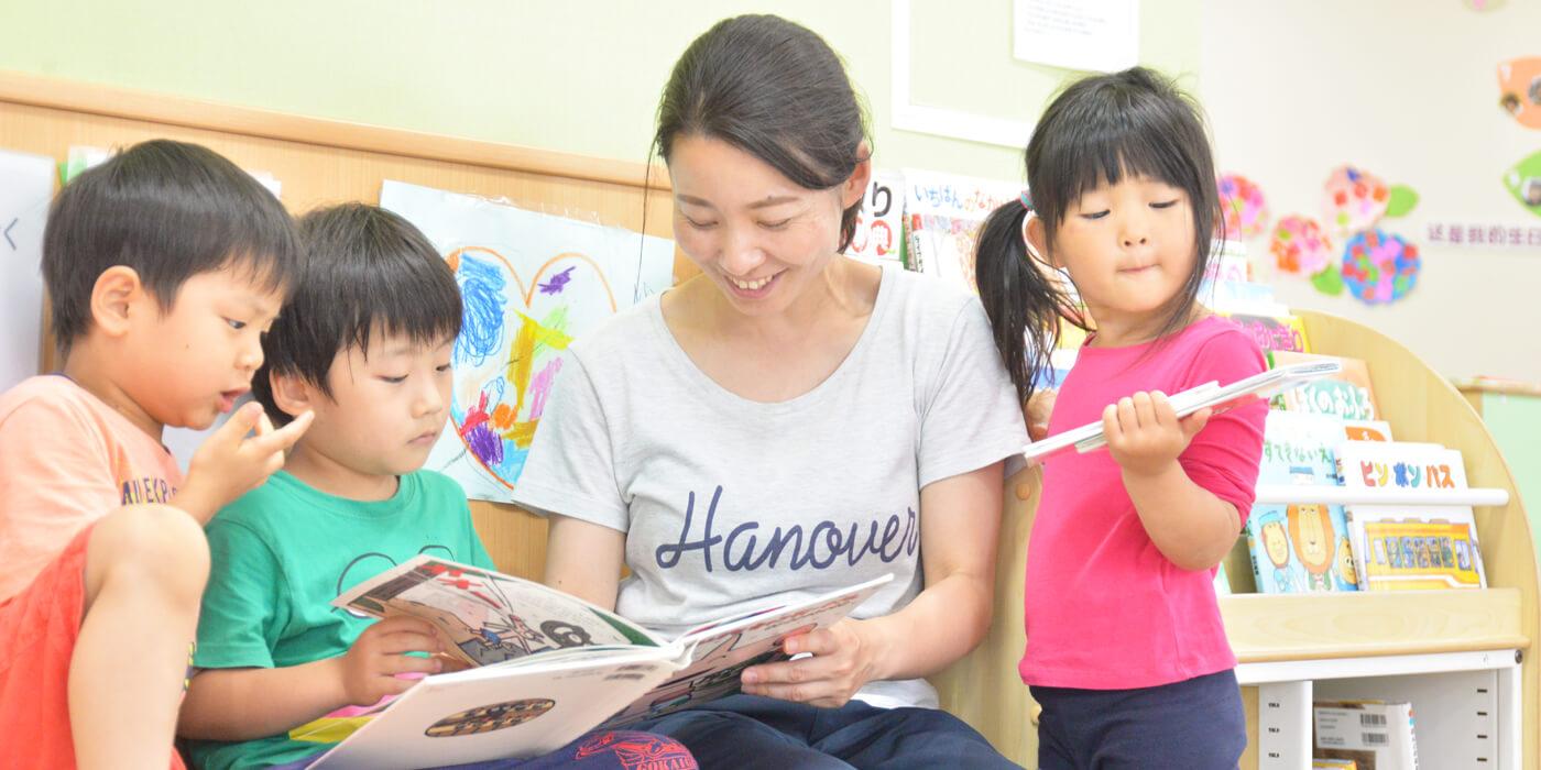 絵本の読み聞かせをする保育士と子どもたち