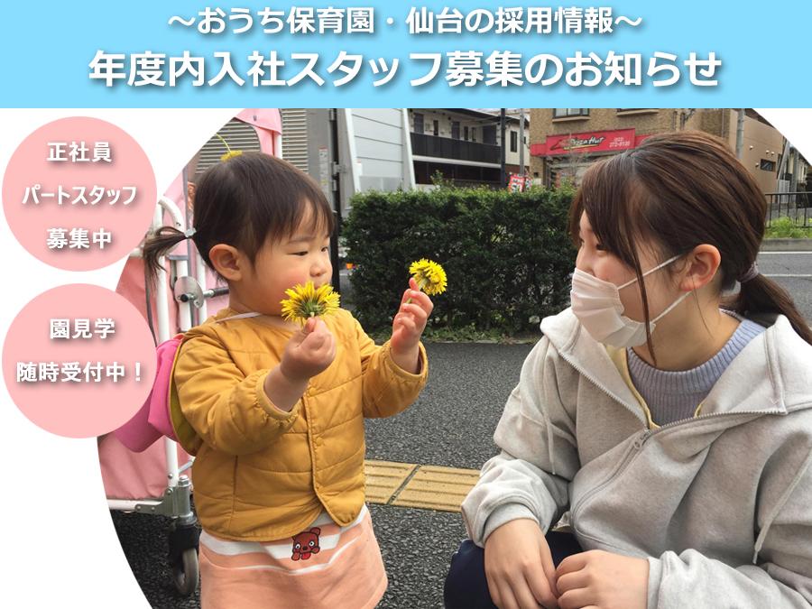 お子さんと先生がたんぽぽを見つけて笑顔の写真